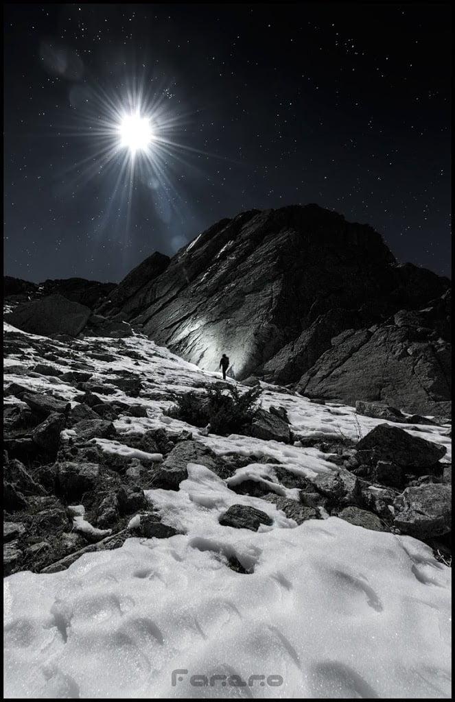 Montañero escalando las montañas madrileñas bajo la luz de la luna