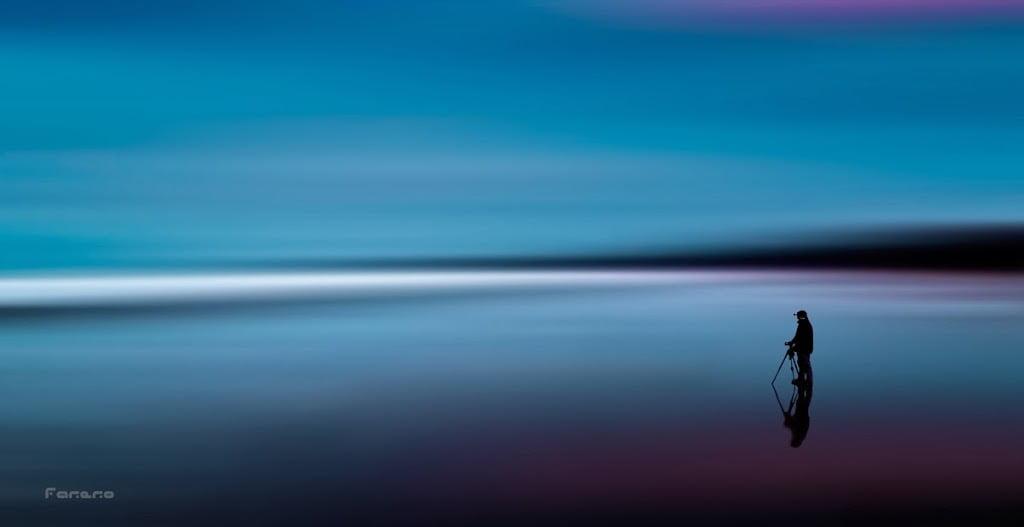 Tutorial fotografía nocturna. Imagen minimalista de un fotografo en medio de una mar azul
