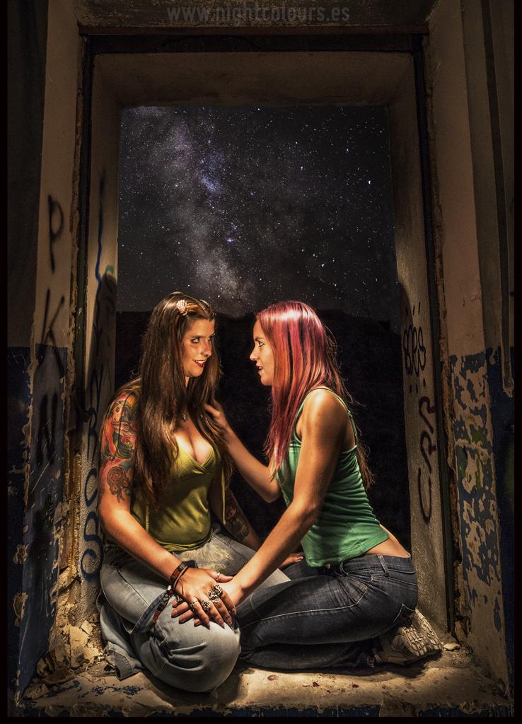 Iluminacion selectiva en escena nocturna entre dos mujeres con una vía lactea de fondo