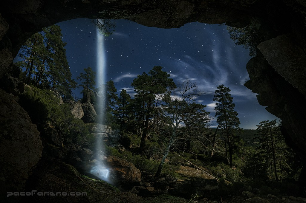Fotografia nocturna de una cueva con una cascada en picos de urbion
